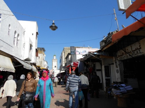 A busy street in the medina. The minaret of Moulay Slimane Mosque is again visible.