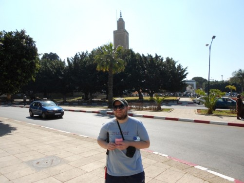 Tony by a main road. The 18th century As Sounna Mosque is opposite, partially obscured by trees. The minaret is visible.