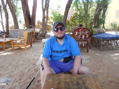 Tony in the backyard of Auberge Menata, sitting in a comfortable chair. Other similar chairs around. Sand under foot. A few trees and plants.