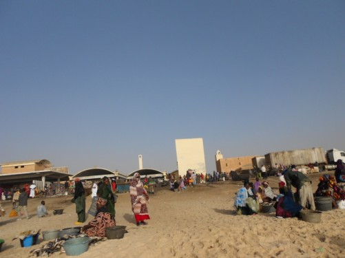 On Nouakchott beach. There are a number of local people, mostly women, with buckets filled with fish. The fish market beyond.
