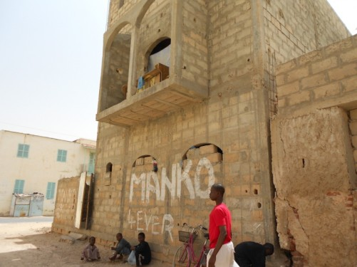 A sandy side street. Children sitting in the shade under a building.