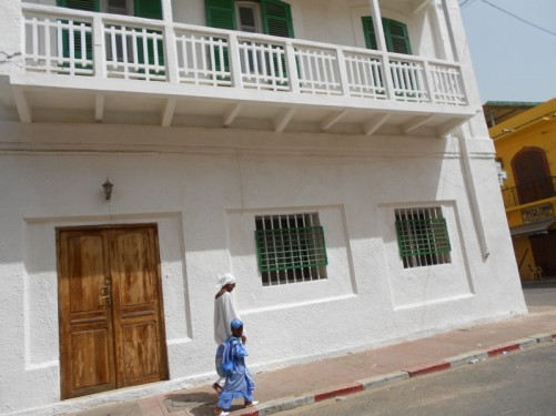 A local Senegalese woman with a child walking along a street. The woman in a white dress and head scarf and the boy in a blue robe.