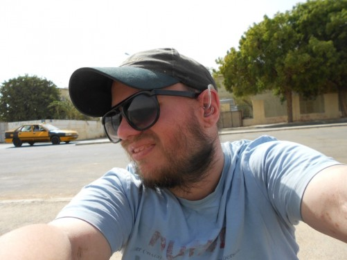 Tony by a road taking a photo of himself.