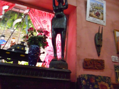 Inside a shop. Traditional craft objects - including a wooden mask and a large wooden figurine.