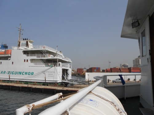 View from the deck of a boat in Dakar port. A car ferry is moored opposite. Shipping containers are stacked up on land nearby.