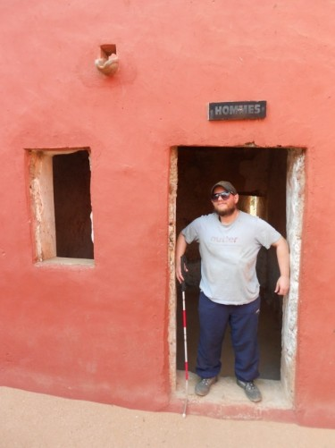 Tony standing in a doorway labelled 'Hommes' (Men). This is where male slaves were held.