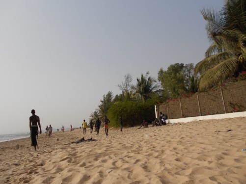 View along the beach. Boys kicking a ball about.