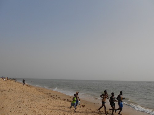 People jogging along the sea shore.
