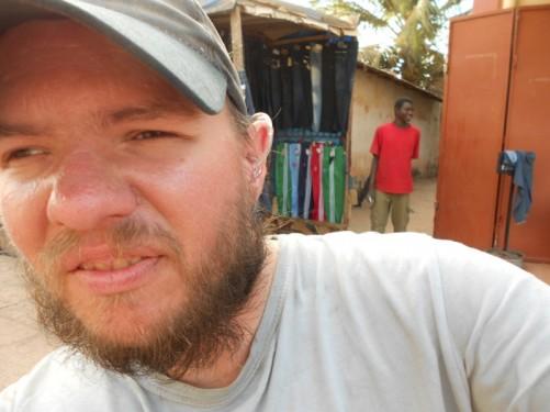 Close-up of Tony at Serrakunda market. A clothes stall behind.