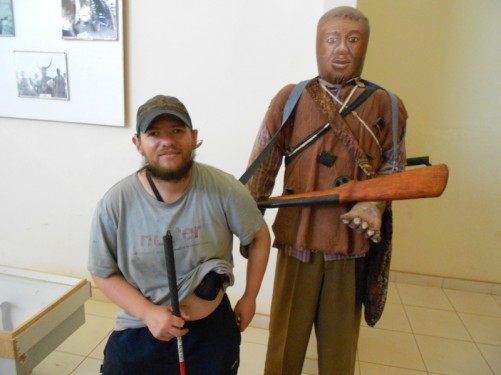 Tony by another mannequin: a man holding a replica rifle.