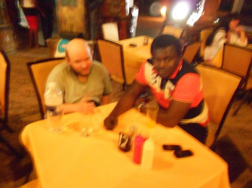Tony sitting at a table with Mohamed in a restaurant, in 'the strip', SENEGAMBIA.