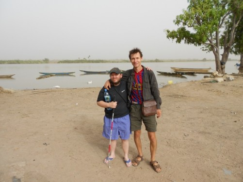 Tony with a fellow traveller from Slovakia by the Gambia River. Several canoes on the river.