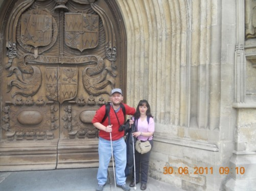 Tony and Tatiana outside a large carved-wooden doorway, the main entrance to Bath Abbey.