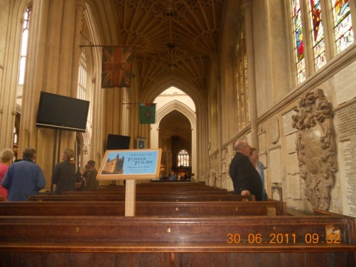 View along the south aisle, Bath Abbey. Pews. Lots of memorial plaques on the wall.