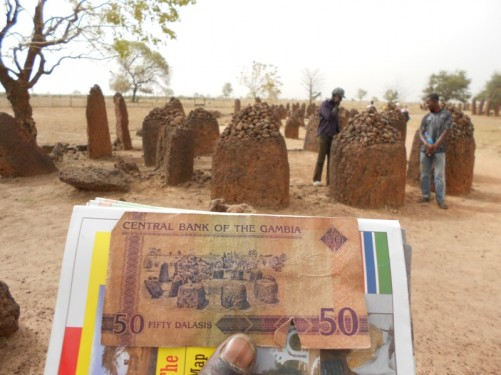 A 50 dalasi Gambian bank note with a stone circle drawing and the actual stone circle depicted in front.