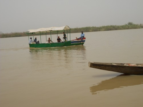 A small tourist boat and a canoe passing by on the river.