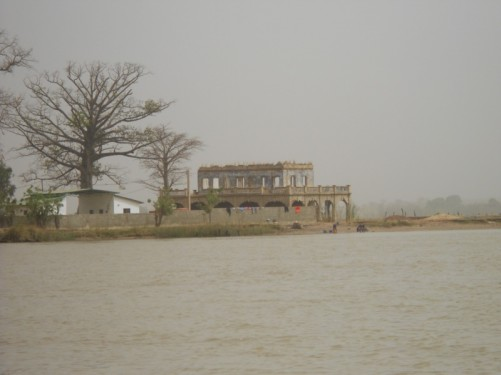 A pair of buildings on the edge of the river seen from the boat.