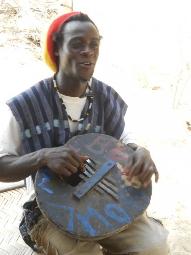 Close-up of Eladji playing the calabash.