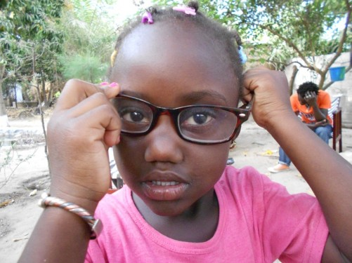 A young local girl called Njaya wearing glasses looking into the camera.