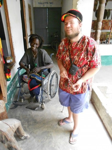 Tony with Joseph, a local Senegalese guy who makes jewellery by hand for a living. Tony holding a necklace.
