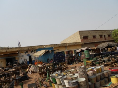 A large collection of buckets, wheelbarrows, and other metal objects stacked up by the road, for sale.