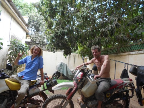 A man and woman sitting on motorbikes at the guesthouse. They are a couple from Germany who were travelling around the whole of Africa for a year.