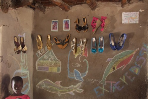 The same room. Several pairs of shoes hung on the wall.