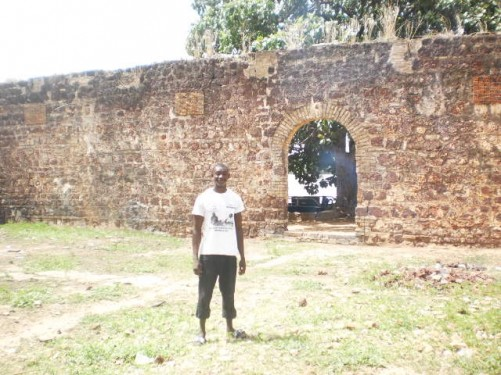 Saigou, behind him is an old wall with a doorway leading to the river.