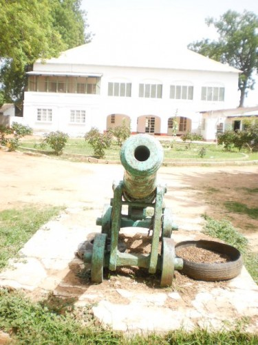 In front of the canon. Behind is a large colonial era building.