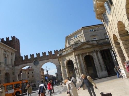 Looking towards the gate into Piazza Bra. The gate is made up of two stone arches, with a clock face in the middle, and a tower to one side.