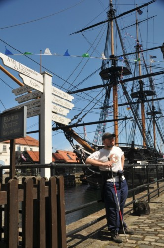 Tony standing on the quayside, HMS Trincomalee and historic buildings in view.