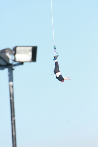 Tony dangling in the air, still attached to the bungee cord.