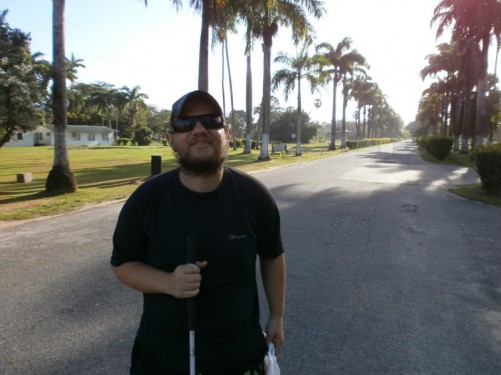 Tony standing on a long straight avenue lined with tall palm trees. This is part of Georgetown's Botanical Gardens.