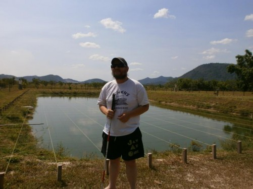 Tony by a large rectangular pond. It has wires laid out in a grid pattern over the top, presumably to stop birds swooping down and catching fish.