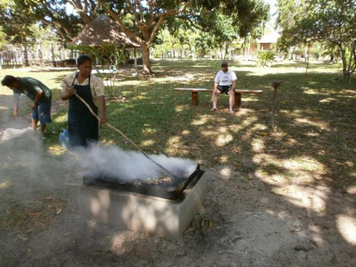 Traditional Peanut roasting: the nuts are in a large metal tray over an open fire. A woman is spreading/turning them with a long stick. Tony sitting on a bench behind.