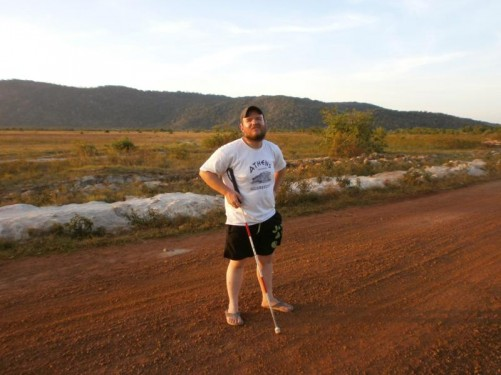 Tony standing on an unsurfaced road. Savannah immediately behind and hills rising up further away.