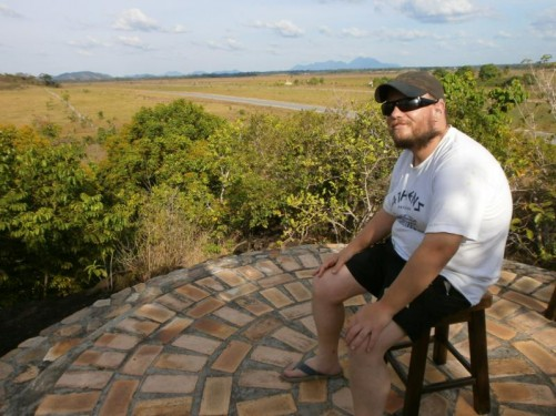 Rock View Lodge rock - a round lookout area with views of the savannah spreading out below. Tony sitting on a stool.