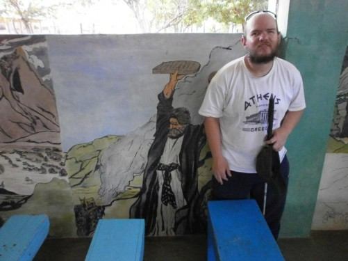 In the village church (or maybe the school?). Tony by rows of wooden benches with paintings of Biblical scenes behind.