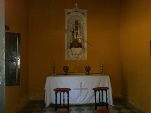 A small altar in the room in which Simón Bolívar died. A table with candlesticks and decorative metal jugs. An alcove containing a religious statue above.