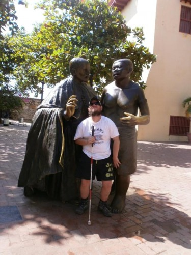 Tony in front of a statue of Saint Peter Claver with a male slave. Saint Peter Claver (1580-1654) was a Spanish Jesuit priest who spent his life helping the slaves who were shipped into Cartagena.
