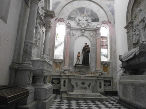 A marble side altar. There is a statue in the middle, probably of Saint Peter Claver. He is holding a small child while giving food, maybe bread, to a boy standing next to him.