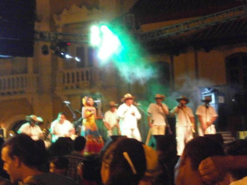 A concert taking place outdoors in Plaza de Bolívar. A group of musicians on stage in front.