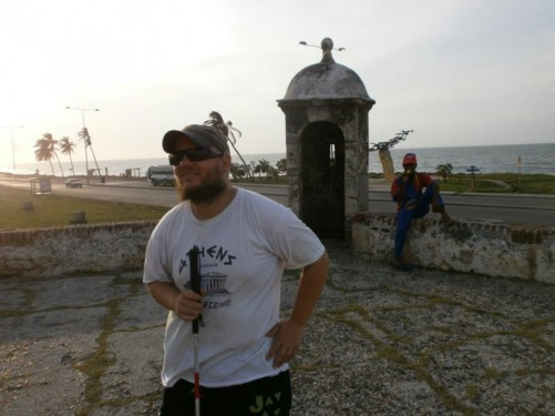 Tony by an historic stone sentry tower overlooking the sea, part of the old city wall defences.