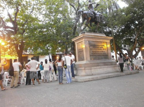 By the Simon Bolívar statue in Plaza de Bolívar. There is a crowd of people watching a classical concert.