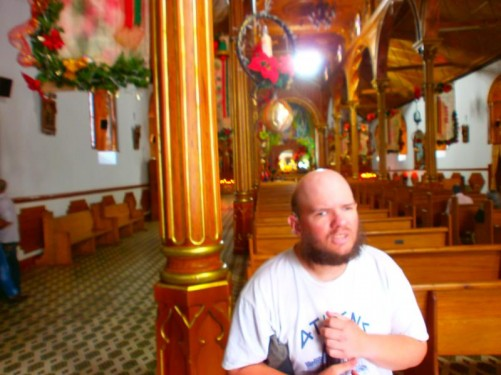 Inside Guatapé's main church. Tony with rows of pews behind him.