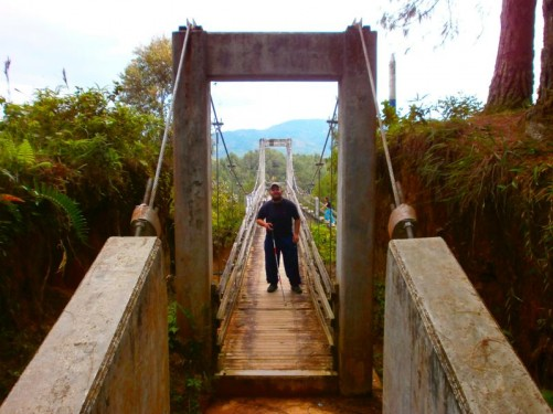 Tony standing on a narrow rickety-looking wooden bridge during the walk from the town to Guatape rock.