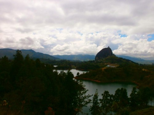 View of Guatapé Rock in the distance with a lake in front. Guatapé Rock (Peñón de Guatapé) is a massive monolithic rock formation around 1.5 miles (2.5 kilometres) from Guatapé town. It is over 200 metres high and is visible throughout the surrounding countryside.