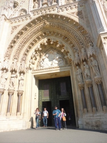 Tony and Tatiana standing in one of the Cathedral's doorways. An elaborately carved stone arch above.
