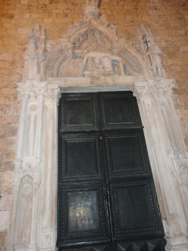 Large doorway with a carved-stone surround, leading into the 14th century Franciscan monastery. It is located in Dubrovnik's old town, near Pile Gate, at one end of the central street known as the Stradum (or Placa).