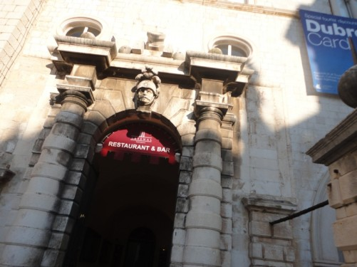 A large doorway off Luža Square. Above it there is a stone head depicting a soldier wearing a helmet.